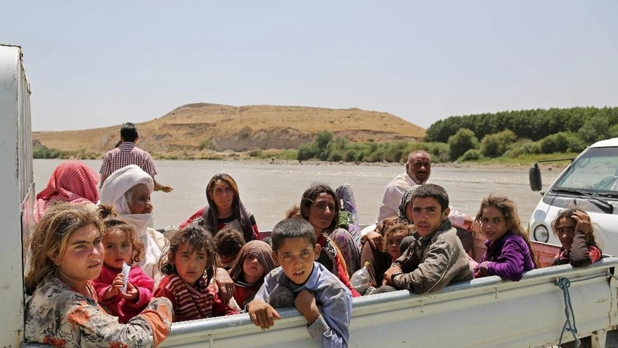 In this Sunday, Aug. 10, 2014, displaced Iraqis from the Yazidi community cross the Iraq-Syria border at Feeshkhabour bridge over Tigris River at Feeshkhabour border point, northern Iraq. Kurdish authorities at the border believe some 45,000 Yazidis passed the river crossing in the past week and thousands more are still stranded in the mountains. (AP Photo/Khalid Mohammed)