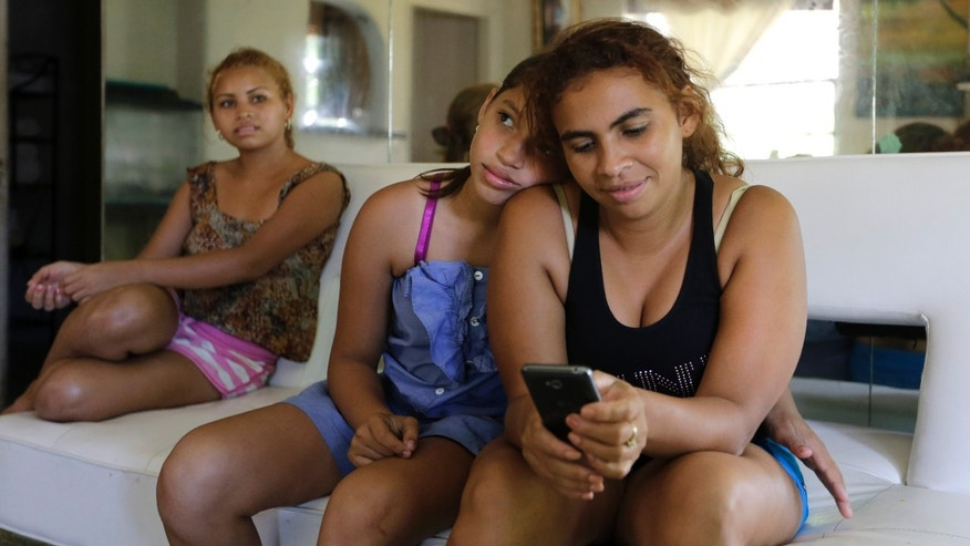 In this July 24, 2014 photo, Nicole Valerio Zelaya, center, 12, sits with her mother Denia Zelaya, right, and her sister Anita Medina Zelaya, 16, at their mother's home in Miami. The family, originally from Honduras, has been reunited in Miami, having arrived separately. As thousands of Central American children have come across the Southwest border these past months, this family found each other again. (AP Photo/Lynne Sladky)