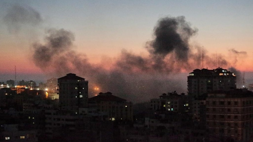 Smoke from fires caused by Israeli strikes, rises over Gaza City, Sunday, Aug. 10, 2014. (AP Photo/Lefteris Pitarakis)