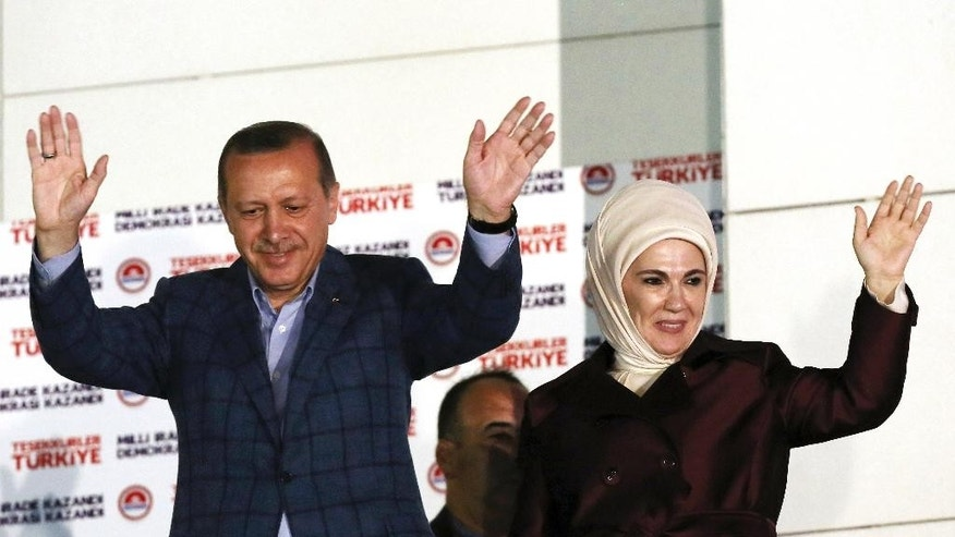 Turkish Prime Minister Recep Tayyip Erdogan and his wife Emine Erdogan acknowledge supporters after Erdogan's election victory, in Ankara, Turkey, Sunday, Aug. 10, 2014. Erdogan won Turkey's first direct presidential election Sunday, striking a conciliatory tone toward critics who fear he is bent on a power grab as he embarks on another five years at the country's helm.(AP Photo/Burhan Ozbilici)