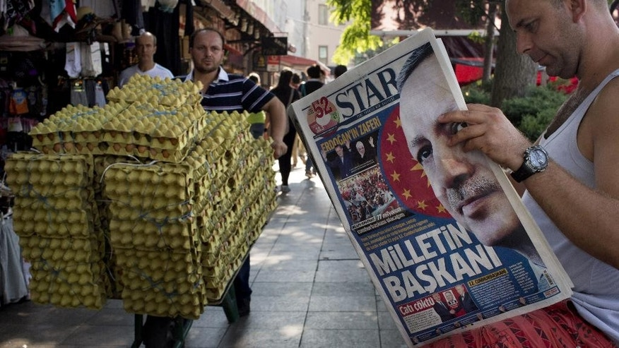 "A man reads a newspaper in central Istanbul, Turkey, on Monday, Aug. 11, 2014. Erdogan won Turkey's first direct presidential election Sunday, striking a conciliatory tone toward critics who fear he is bent on a power grab as he embarks on another five years at the country's helm. The newspaper's front page headline reads a ""President of the Nation"". (AP Photo/Emilio Morenatti)"