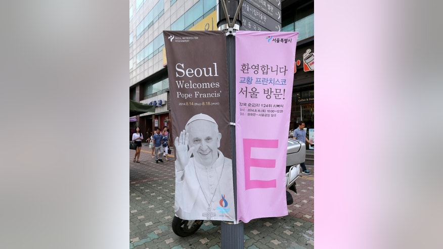 A banner showing Pope Francis is displayed on the street in Seoul, South Korea, Monday, Aug. 11, 2014.  Pope Francis is scheduled to make a five-day trip to South Korea, starting Aug. 14 to participate in a Catholic youth festival and to preside over a beatification ceremony for 124 Korean martyrs.(AP Photo/Ahn Young-joon)