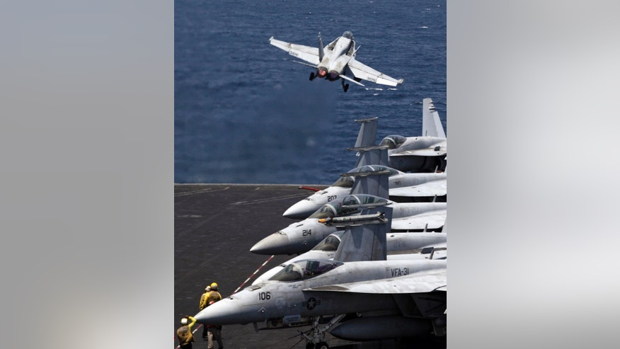 A U.S. F/A-18 fighter jet takes off for Iraq from the flight deck of the U.S. Navy aircraft carrier USS George H.W. Bush in the Persian Gulf, Monday, Aug. 11, 2014. U.S. military officials said American fighter aircraft struck and destroyed several vehicles Sunday that were part of an Islamic State group convoy moving to attack Kurdish forces defending the northeastern Iraqi city of Irbil. (AP Photo/Hasan Jamali)