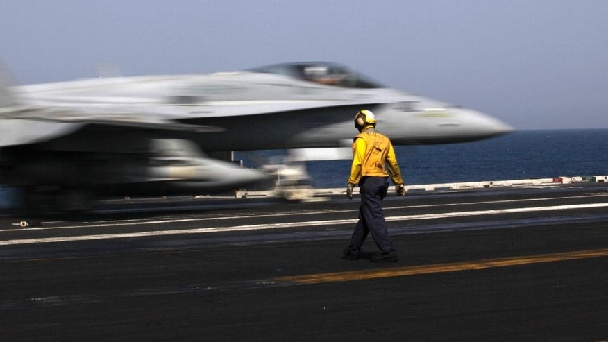 A U.S. F/A-18 fighter jet takes off for Iraq from the flight deck of the U.S. Navy aircraft carrier USS George H.W. Bush, in the Persian Gulf, Monday, Aug. 11, 2014.  U.S. military officials say American fighter aircraft struck and destroyed several vehicles Sunday that were part of an Islamic State group convoy moving to attack Kurdish forces defending the northeastern Iraqi city of Irbil. (AP Photo/Hasan Jamali)