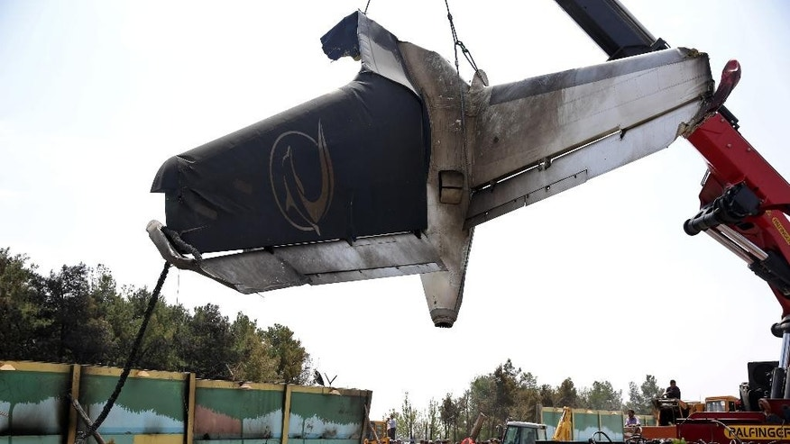A firefighting crane lifts the tail section of a passenger plane which crashed near the capital Tehran, Iran, Sunday, Aug. 10, 2014.  The Sepahan Air Iran-140 regional plane crashed Sunday killing tens of people onboard, shortly after takeoff  from Tehran's Mehrabad airport on its way to Tabas, a town in eastern Iran, state media reported. (AP Photo/Ebrahim Noroozi)