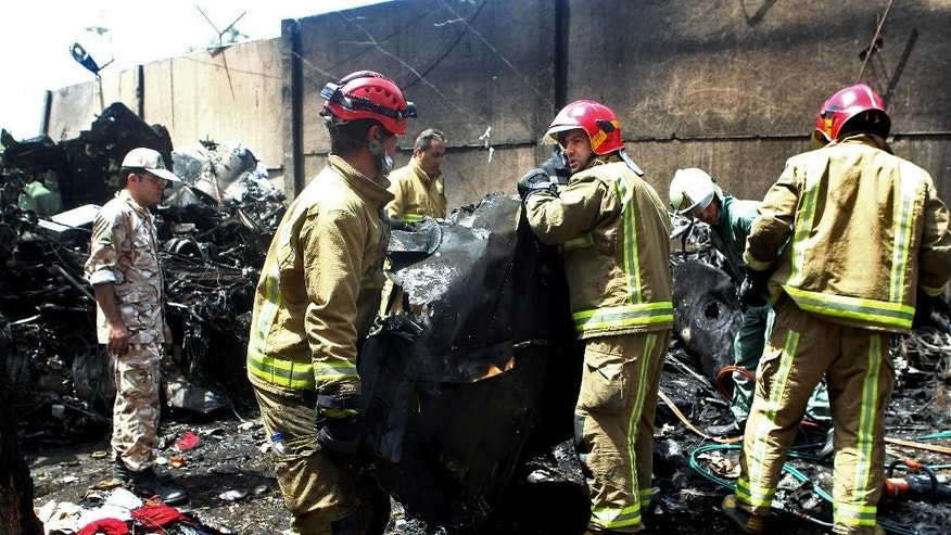 Iranian security and rescue personnel inspect the site of a passenger plane crash near the capital Tehran, Iran, Sunday, Aug. 10, 2014. An Iranian passenger plane crashed Sunday while taking off from an airport near the capital, killing tens of people onboard, state media reported. (AP Photo/Ebrahim Noroozi)