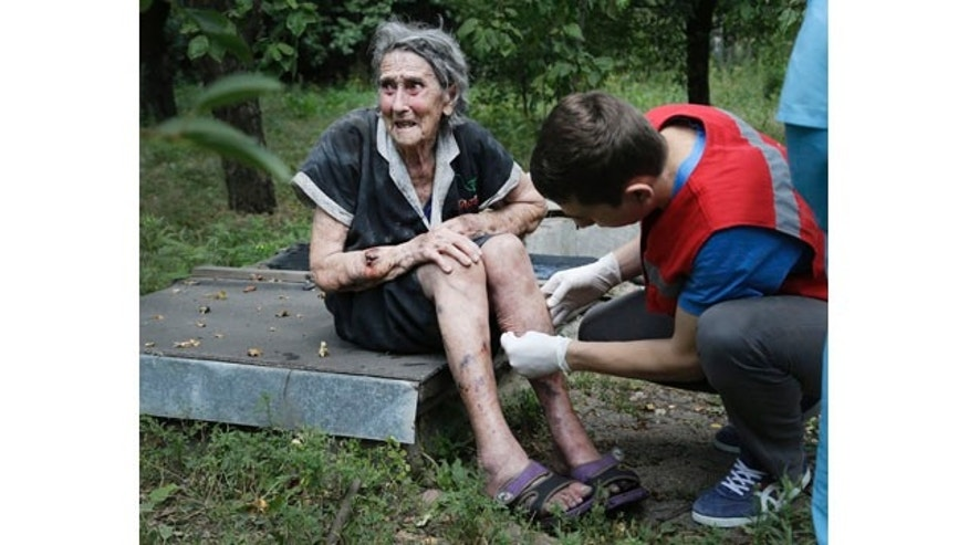 August 10, 2014: A wounded Ukrainian woman receives treatment after shelling in Donetsk. One person was killed and 10 injured in shelling that started early Sunday morning and continued into the day, city council spokesman Maxim Rovinsky told The Associated Press. (AP Photo/Sergei Grits)