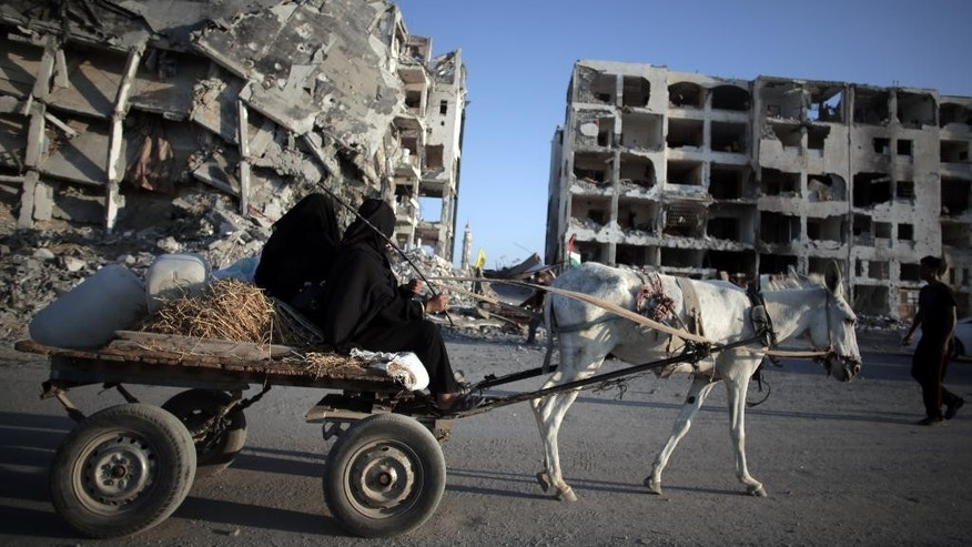Two Palestinian women ride a donkey cart past the destroyed Nada Towers residential neighborhood in the town of Beit Lahiya, northern Gaza Strip, Monday, Aug. 11, 2014.  A new temporary truce took hold, Monday, in the monthlong war pitting the Israeli military against rocket-firing Hamas militants as negotiators from Israel and the Hamas militant group resumed indirect talks in Egypt on Monday. (AP Photo/Khalil Hamra)