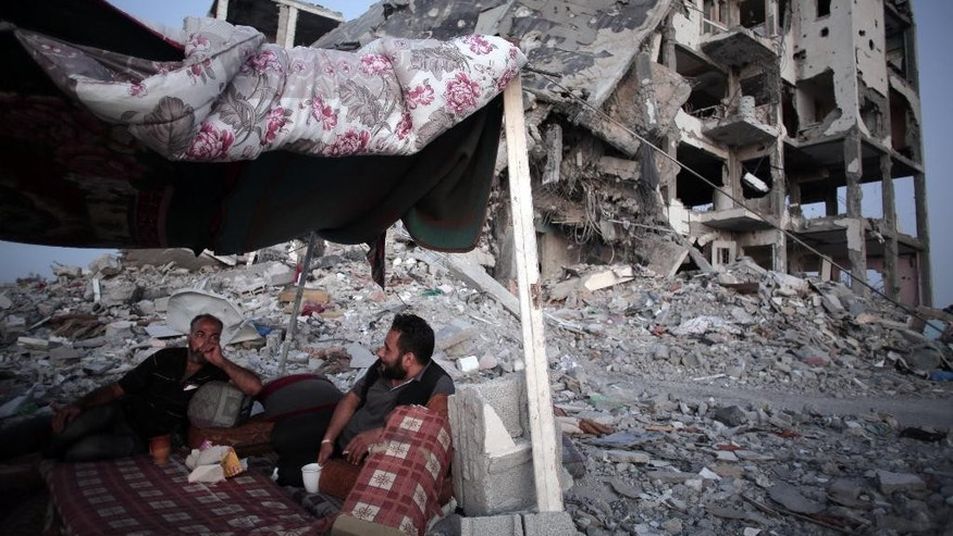 Palestinian Ziad Rizk, 38, left, sits with others in a shelter made of a blanket stretched over four boles next to one of the destroyed Nada Towers, where he lost his apartment and clothes shop, in the town of Beit Lahiya, northern Gaza Strip, Monday, Aug. 11, 2014. (AP Photo/Khalil Hamra)