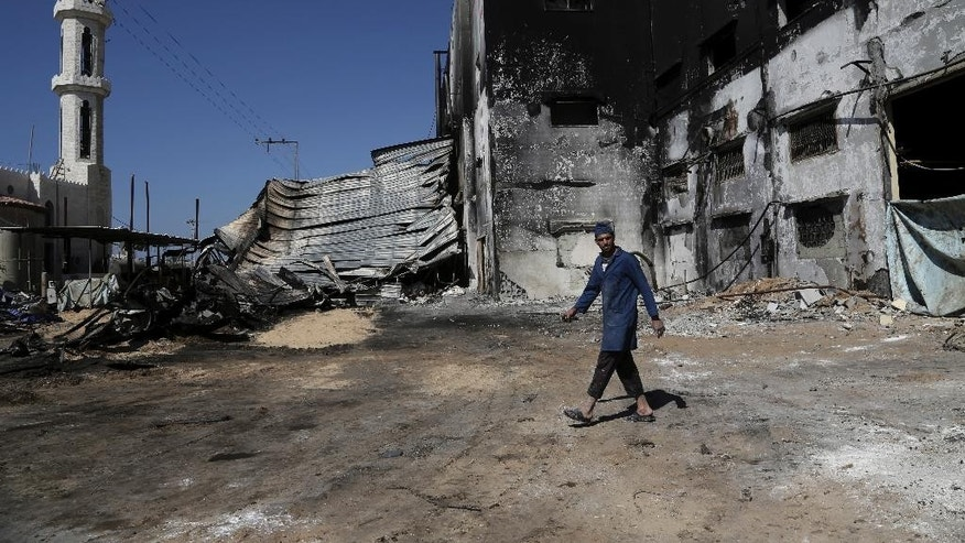 Ahmad Baraka, 25, a Palestinian worker at Al Awda snack food factory inspects the damage and burned factory in Deir el-Balah, central Gaza Strip. The factory owner, Mohammed al-Telbani, lost his life's work during the Gaza war after Israeli shells slammed into his four-story factory, one of Gaza's largest, sparking a fire that engulfed vats of margarine and sacks of cocoa powder. Al-Telbani and others in Gaza say anything short of a complete opening of Gaza's borders, after seven years of closure by Israel and Egypt, will do little to change their lives. (AP Photo/Adel Hana)