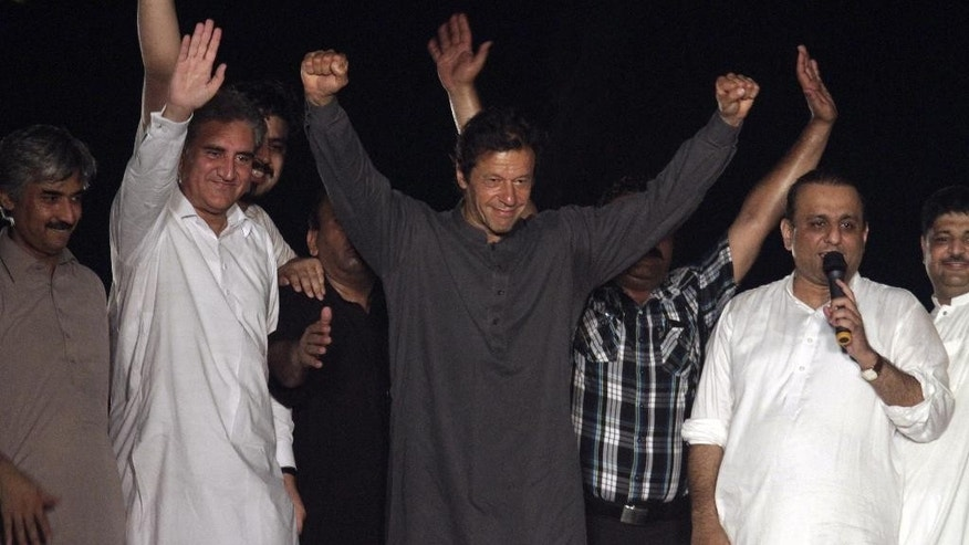 Aug. 11, 2014: Pakistan's cricketer-turned-politician Imran Khan, center, surrounded by aids and supporters, greets his followers outside his home, in Lahore, Pakistan. (AP)