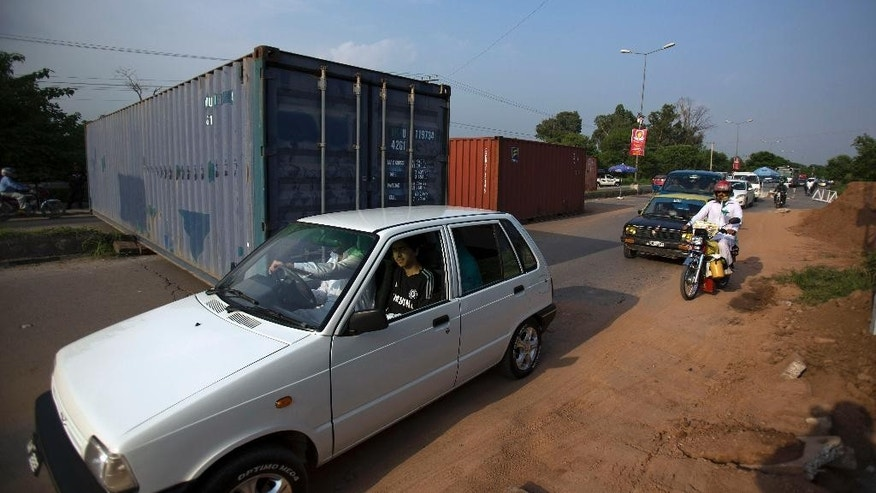 Pakistani authorities place containers on the road leading to Parliament House to stop activists of Pakistan Tehreek-i-Insaf, chaired by Pakistan's cricketer-turned politician Imran Khan and supporters of Canadian Muslim cleric Tahirul Qadri, in Islamabad, Pakistan, Monday, Aug. 11, 2014. Khan and Qadri announced that they will hold a huge protest rally in capital on Aug 14 against alleged massive rigging in the 2013 general elections. (AP Photo/B.K. Bangash)