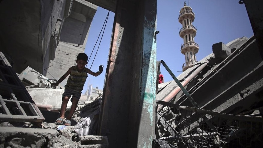 In this Saturday, Aug. 9, 2014 photo, a Palestinian boy walks amid the rubble of the Al-Qassam Mosque that was hit by an Israeli airstrike, in the Nuseirat refugee camp, central Gaza Strip. Israel has hit and destroyed 63 mosques in Gaza in its month-old war with Hamas, Palestinian officials say. The reason, Israel says, is that Hamas is using mosques to stockpile weapons and rocket launchers and hide tunnels. Gaza's Hamas rulers deny the accusations. But in its determination to go after what it says are militant arsenals, Israel is throwing aside any reluctance it had in the past to hit religious sites for fear of a diplomatic backlash. (AP Photo/Khalil Hamra)