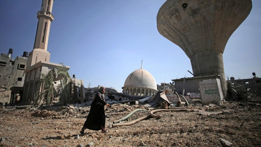 In this Friday, Aug. 1, 2014 photo, a Palestinian woman walks past a mosque destroyed by Israeli strikes in the village of Khuzaa, near Khan Younis, southern Gaza Strip. Israel has hit and destroyed 63 mosques in Gaza in its month-old war with Hamas, Palestinian officials say. The reason, Israel says, is that Hamas is using mosques to stockpile weapons and rocket launchers and hide tunnels. Gaza's Hamas rulers deny the accusations. But in its determination to go after what it says are militant arsenals, Israel is throwing aside any reluctance it had in the past to hit religious sites for fear of a diplomatic backlash. (AP Photo/Khalil Hamra)