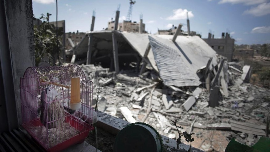 In this Saturday, Aug. 9, 2014 photo, a bird in a cage sits on a window sill overlooking the Zeitoun Martyrs Mosque that was destroyed in Israeli strikes in the Zeitoun neighborhood of Gaza City. Israel has hit and destroyed 63 mosques in Gaza in its month-old war with Hamas, Palestinian officials say. The reason, Israel says, is that Hamas is using mosques to stockpile weapons and rocket launchers and hide tunnels. Gaza's Hamas rulers deny the accusations. But in its determination to go after what it says are militant arsenals, Israel is throwing aside any reluctance it had in the past to hit religious sites for fear of a diplomatic backlash. (AP Photo/Khalil Hamra)