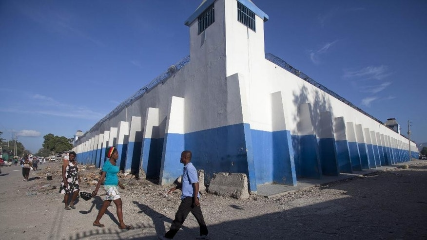 Pedestrians walk past a watch tower of the main prison in Croix-des-Bouquets, Haiti, Monday, August 11, 2014.  An attack on the prison on the outskirts of the capital to free the son of a prominent businessman being held on kidnapping charges resulted in the escape of 329, officials said Monday. Police were searching throughout the country for the escaped prisoners and have also asked for help from Interpol as well as authorities in the neighboring Dominican Republic and nearby Jamaica because some of the men may have fled abroad, National Police Chief Godson Orleus said in a news conference in Port-au-Prince. (AP Photo/Dieu Nalio Chery)