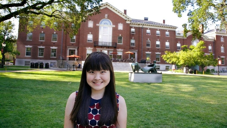 In this Thursday, July 10, 2014 photo, Lisa Li, a high school student at the U.S. prep school Lawrence Academy in Groton, Mass., poses for a photo outside the Stephen Robert Campus Center on the Brown University Campus in Providence, RI. High schoolers want to escape the rat race in China, where students often study late into the night with little opportunity for extracurricular activities. They also believe studying in the U.S. will help them snag coveted spots at more prestigious American colleges. Li said she felt like a failure if she didn't get the top test score in her class in Beijing. Her academic work in the U.S. is also rigorous, but she says she doesn't feel the same kind of pressure, and is now encouraged to explore other interests - like music composition. (AP Photo/Stephan Savoia)