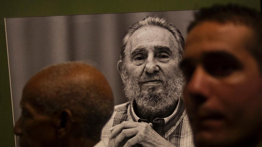 People attend an exhibition of photographs of Cuba's former president Fidel Castro, made by photographer Roberto Chile at the Jose Marti Memorial in Havana, Cuba, Tuesday, Aug. 12, 2014. Castro will celebrate his 88th birthday on Wednesday. (AP Photo / Ramon Espinosa)