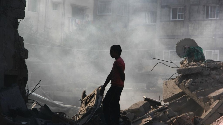 FILE - In this Saturday, Aug. 2, 2014 file photo, a Palestinian looks for his belongings after a house was destroyed in an Israeli strike in Rafah, southern Gaza Strip, Saturday. (AP Photo/Hatem Ali, File)