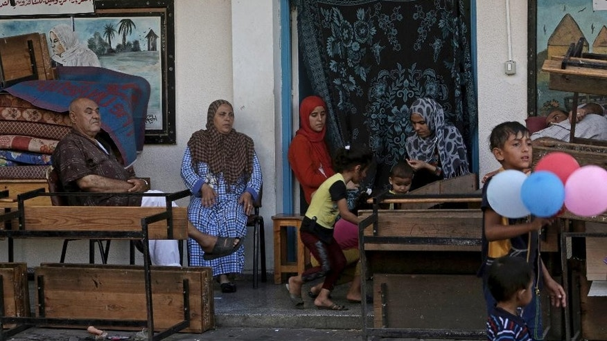 Displaced Palestinian family members pass their time at the U.N. school where they sought refuge during the war, in Beit Lahiya, in the northern Gaza Strip, Tuesday, Aug. 12, 2014. Tens of thousands of Palestinians have been displaced in the Israel-Hamas war that began July 8, at least 10,000 housing units have been destroyed and many have found refuge at U.N. schools turned into shelters. (AP Photo/Adel Hana)