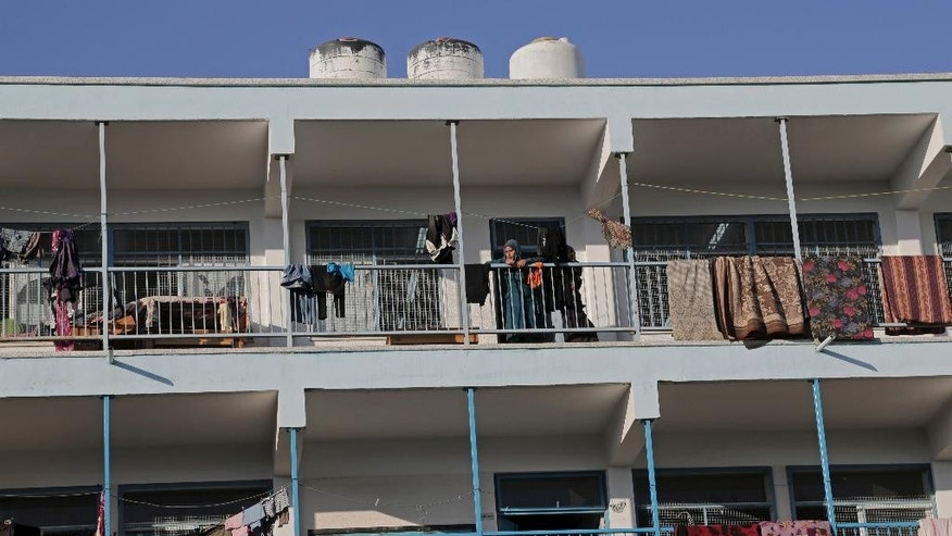 A displaced Palestinian female stands on the balcony of the U.N. school where her family sought refuge during the war, in Beit Lahiya, in the northern Gaza Strip, Tuesday, Aug. 12, 2014. Tens of thousands of Palestinians have been displaced in the Israel-Hamas war that began July 8, at least 10,000 housing units have been destroyed and many have found refuge at U.N. schools turned into shelters. (AP Photo/Adel Hana)