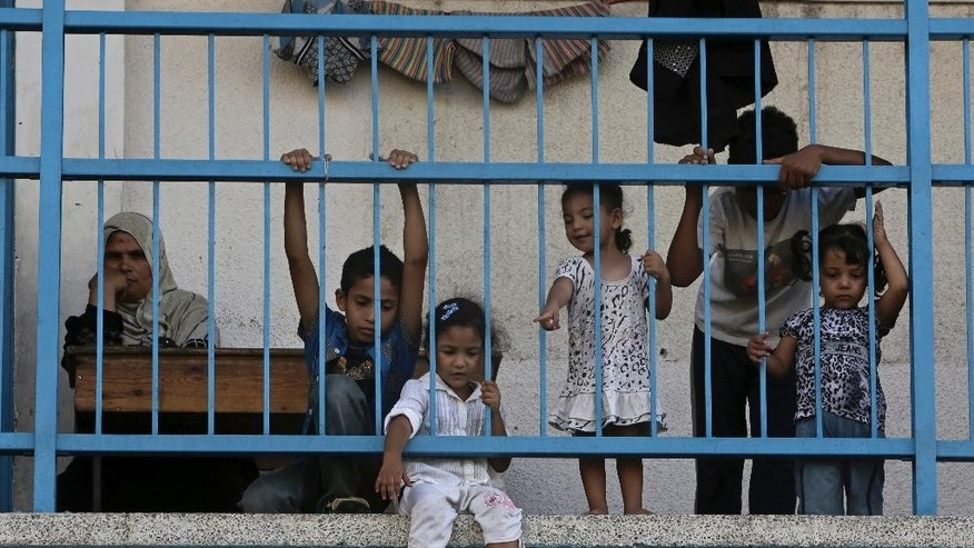 Displaced Palestinian children play on the balcony of the U.N. school where their family sought refuge during the war, in Beit Lahiya, in the northern Gaza Strip, Tuesday, Aug. 12, 2014. Tens of thousands of Palestinians have been displaced in the Israel-Hamas war that began July 8, at least 10,000 housing units have been destroyed and many have found refuge at U.N. schools turned into shelters. (AP Photo/Adel Hana)