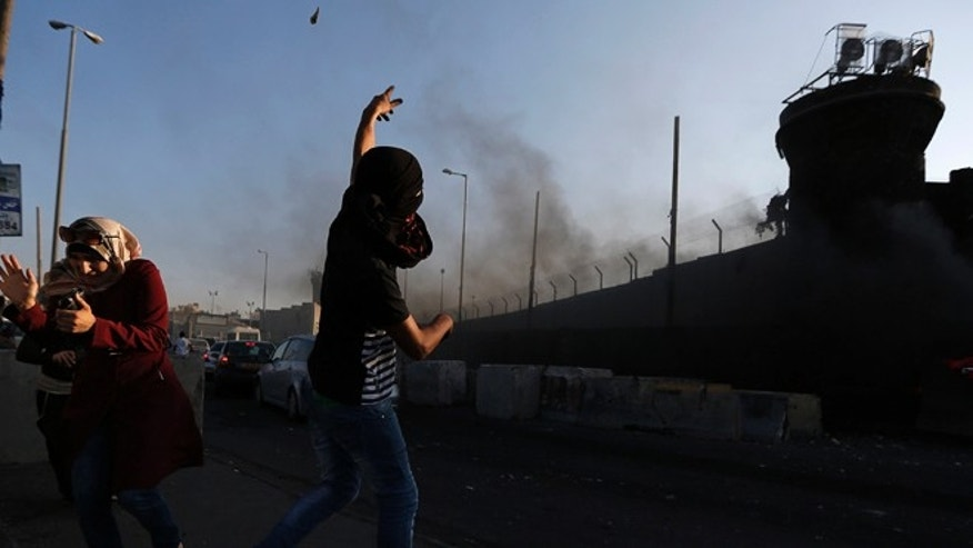 August 13, 2014: A Palestinian hurls stones toward Israeli soldiers during a protest against the Israeli offensive in Gaza, at Qalandia checkpoint near the West Bank city of Ramallah. The threat of renewed war in Gaza loomed on Wednesday as the clock ticked toward the end of a three-day ceasefire with no sign of a breakthrough in indirect talks in Cairo between Israel and the Palestinians.