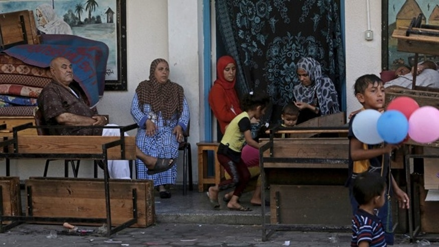 August 12, 2014: Displaced Palestinian family members pass their time at the U.N. school where they sought refuge during the war, in Beit Lahiya, in the northern Gaza Strip. (AP Photo/Adel Hana)
