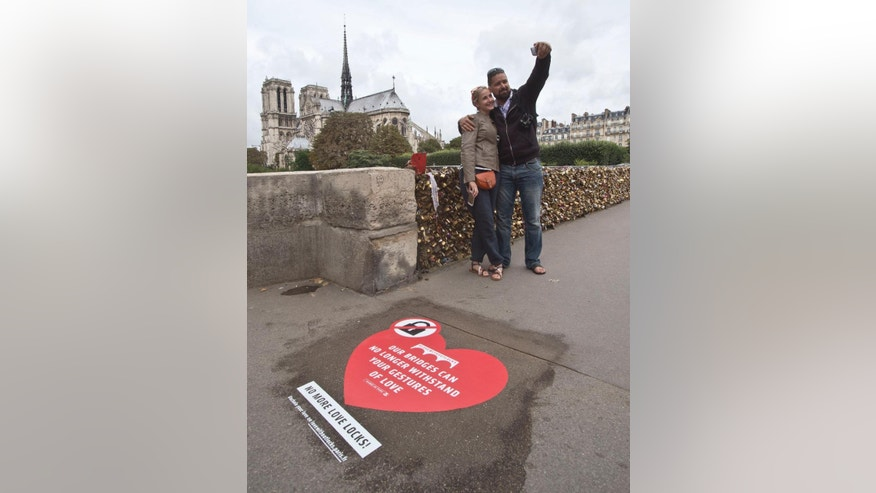 Latvian's Regina and Vadim Medvedev from Riga, on honeymoon in Paris, pose for a selfie on the Pont de l'Archeveche in Paris next to a giant sticker in Paris, Wednesday, Aug. 13, 2014. Paris is hoping to persuade visiting couples to end the recent and unwelcome tradition of fixing padlocks to the Pont de l'Archeveche. With giant stickers in three languages in French, English and Spanish. Paris began its 'Lovewithoutlocks' campaign, saying the city's famed bridge could not withstand the thousands of padlocks that cling to every available surface. (AP Photo/Michel Euler)