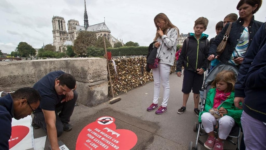 Passers-by look on municipality workers, as they fix a giant sticker on the sidewalk of the Pont de l'Archeveche in Paris, Wednesday, Aug. 13, 2014. Paris is hoping to persuade visiting couples to end the recent and unwelcome tradition of fixing padlocks to the Pont de l'Archeveche. With giant stickers in three languages in French, English and Spanish. Paris began its 'Lovewithoutlocks' campaign, saying the city's famed bridge could not withstand the thousands of padlocks that cling to every available surface. (AP Photo/Michel Euler)