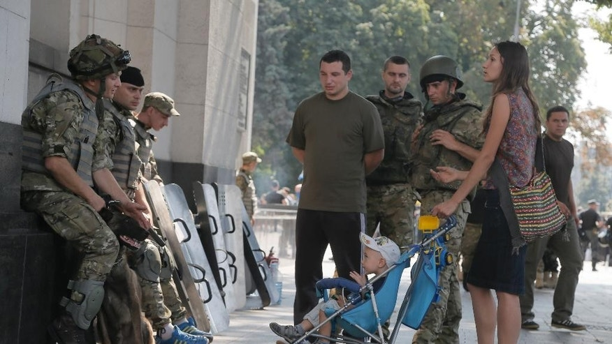 In this picture taken on Tuesday, Aug. 12, a woman with a child talks to Ukraine's National Guard soldiers who have returned from combat operations against pro-Russian separatists in Ukraine's east, near the walls of the parliament in Kiev, Ukraine. Since a separatist insurgency broke out in eastern Ukraine in March, entire swaths of Ukrainian society _ either through a government summons or their own patriotism _ have suddenly been thrust into battle, many of them with little or no combat experience. With the government desperate for more fighters and medics, a draft has brought in a wave of needed additions to what had been a neglected army. And amid a surge of patriotic indignation tipping over into martial fervor, volunteer battalions have proven an indispensable boost as well. (AP Photo/Efrem Lukatsky)