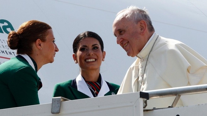 Aug 13, 2014: Pope Francis is welcomed by two hostesses as he boards a plane to South Korea, at Rome's Fiumicino international airport. (AP)