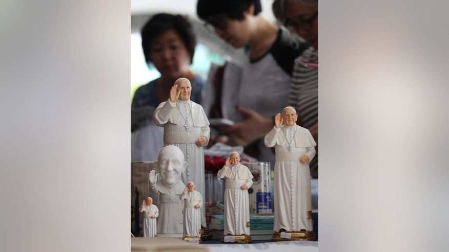 Statues of Pope Francis are displayed at a souvenir shop at Myeongdong Cathedral in Seoul, South Korea, Wednesday, Aug. 13, 2014. Pope Francis is scheduled to make a five-day trip to South Korea, starting Aug. 14 to participate in a Catholic youth festival and to preside over a beatification ceremony for 124 Korean martyrs. (AP Photo/Ahn Young-joon)