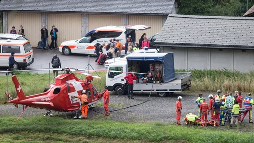Aug.13, 2014: Rescue forces recover a victim of today's train crash, right, near Tiefencastel, Switzerland. A passenger train traveling from St Moritz to Chur in eastern Switzerland has been derailed by a landslide, local police have announced.
