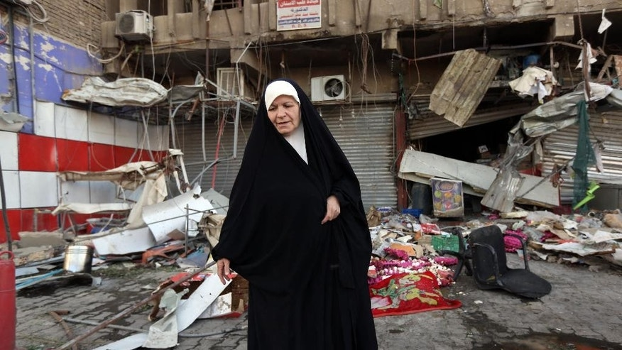 An Iraqi woman pauses at the site of a car bomb attack in central Baghdad's busy commercial Karradah neighborhood, Iraq, Wednesday, Aug 13, 2014. On Tuesday night, a car bomb exploded in the commercial district of Karrada, killing and wounded scores of people. (AP Photo/Hadi Mizban)