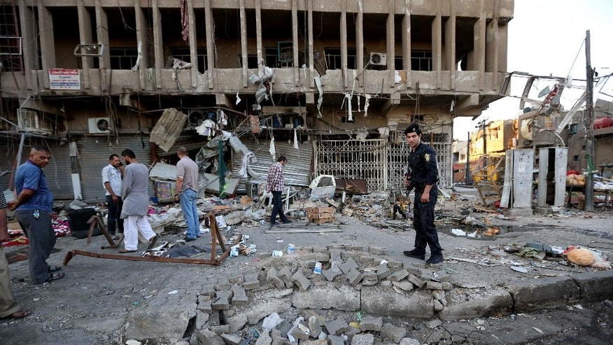 An Iraqi policeman and civilians inspect the site of a car bomb attack in central Baghdad's busy commercial Karradah neighborhood, Iraq, Wednesday, Aug 13, 2014. On Tuesday night, a car bomb exploded in the commercial district of Karrada, killing and wounded scores of people. (AP Photo/Hadi Mizban)