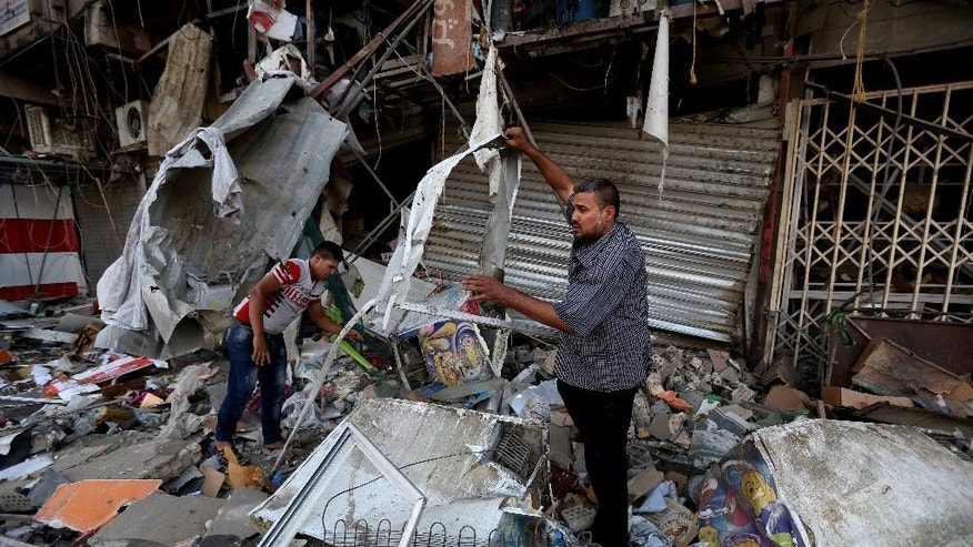 Civilians salvage what they can of their belongings at the site of a car bomb attack in central Baghdad's busy commercial Karradah neighborhood, Iraq, Wednesday, Aug 13, 2014. On Tuesday night, a car bomb exploded in the commercial district of Karrada, killing and wounded scores of people. (AP Photo/Hadi Mizban)