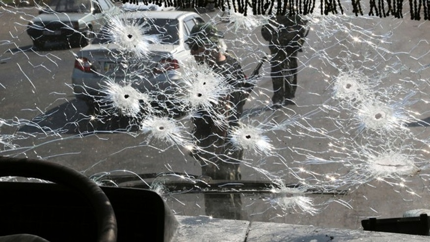 Aug. 13, 2014: Pro-Russian rebels standing at a block-post on the outskirts of Donetsk are seen through the bullet riddled windshield of a bus.