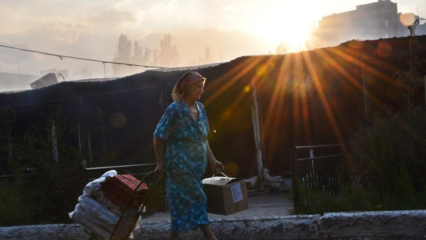 A woman walks by a burning local market after shelling in the town of Yasynuvata, near the rebel stronghold of Donetsk, eastern Ukraine, Tuesday, Aug. 12, 2014. With a theatrical flourish, Russia on Tuesday dispatched hundreds of trucks covered in white tarps and sprinkled with holy water on a mission to deliver aid to a desperate rebel-held zone in eastern Ukraine. (AP Photo/Mstyslav Chernov)