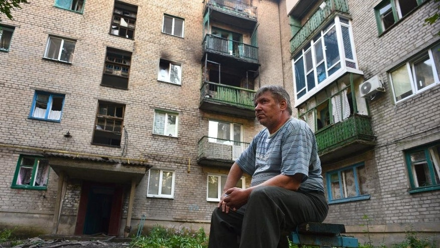 A local man sits near the house where his son was killed by shelling in the town of Yasynuvata, near the rebel stronghold of Donetsk, eastern Ukraine, Tuesday, Aug. 12, 2014. For many people this war is personal and has a profound effect on their lives, but with a theatrical flourish, Russia on Tuesday dispatched some hundreds of trucks covered in white tarps and sprinkled with holy water on a mission to deliver aid to a rebel-held zone in eastern Ukraine. (AP Photo/Mstyslav Chernov)