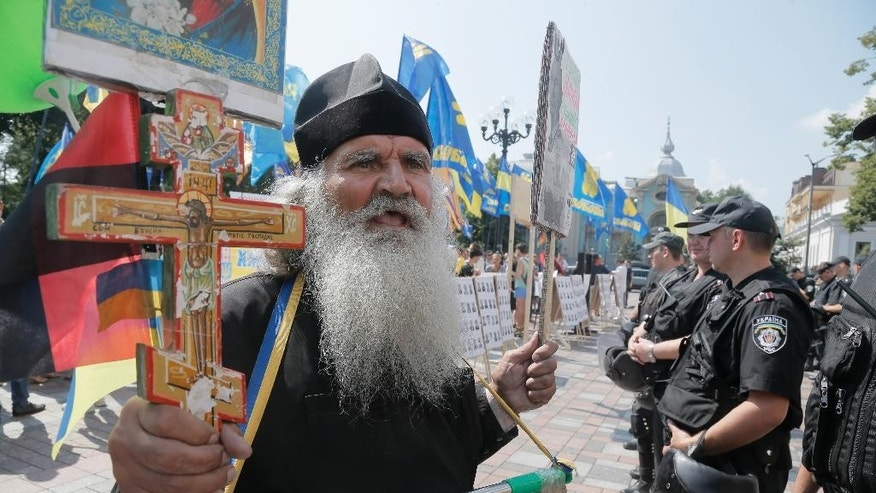 An Orthodox priest holds a cross as he demands sanctions against Russia in front of riot police near the parliament building in Kiev, Ukraine, Tuesday, Aug. 12, 2014. (AP Photo/Efrem Lukatsky)