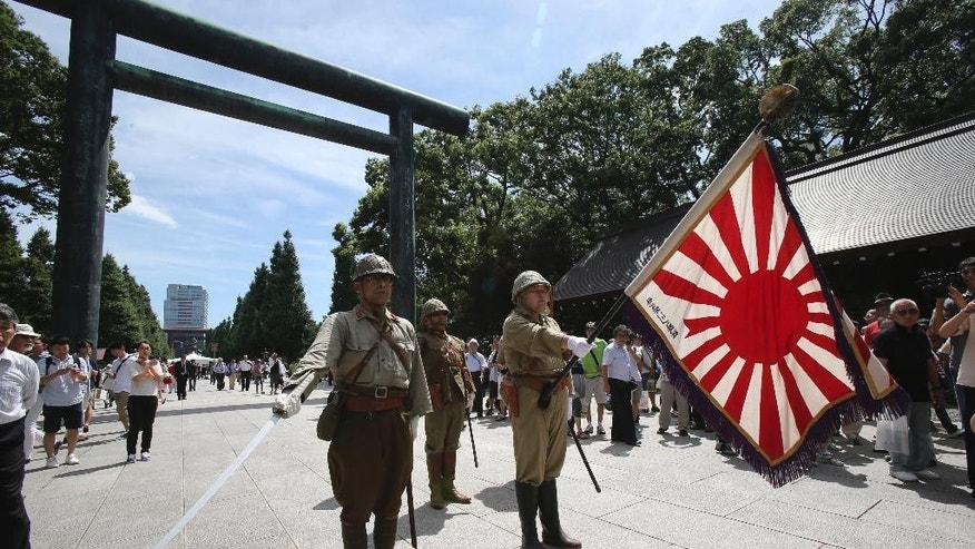 Japanese men clad in outdated military costume march in to pay respects to the country's war dead at the Yasukuni Shrine in Tokyo, Friday, Aug. 15, 2014. Japan marks the 69th anniversary of its surrender in World War II. Friday. (AP Photo/Koji Sasahara)