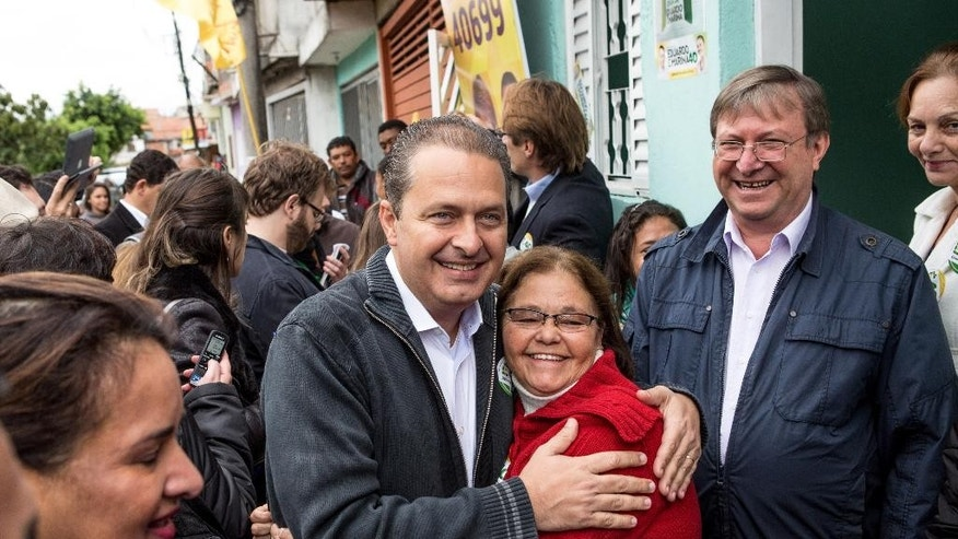 In this July 29, 2014 photo released by the Partido Socialista Brasilero, PSB, Brazilian presidential candidate Eduardo Campos, poses for a photo with a supporter, during a campaign rally, in Osasco, Brazil. The PSB presidential candidate died Wednesday, Aug. 13, 2014, when the small plane that was carrying him and several campaign officials plunged into a residential neighborhood in the port city of Santos, a City Hall official there said. (AP Photo/Partido Socialista Brasilero)