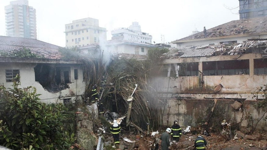 Firefighters work at the crash site of a small plane that was carrying Brazilian presidential candidate Eduardo Campos and several campaign officials, in Santos, Brazil, Wednesday, Aug. 13, 2014. Campos died Wednesday when the small plane that was carrying him and several campaign officials plunged into a residential neighborhood in the port city of Santos, a City Hall official there said. (AP Photo/A Tribuna,Walter Mello)