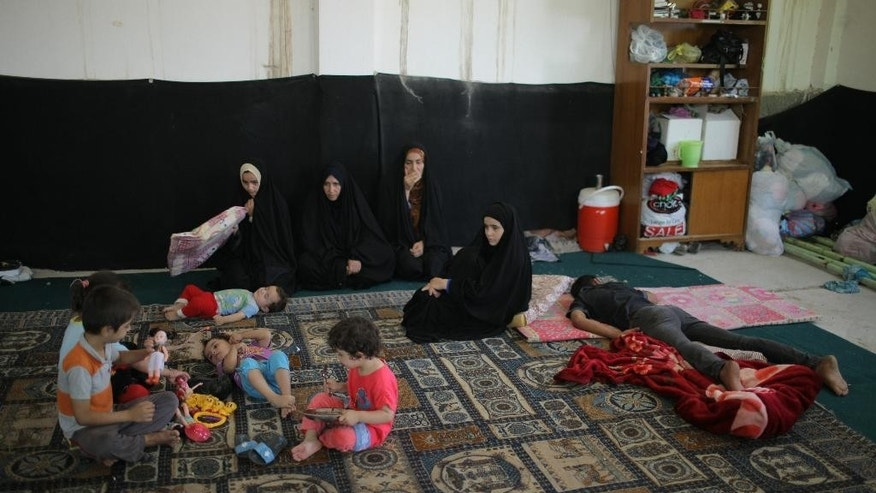 In this Aug. 6, 2014, photo, displaced Iraqis who fled from their towns after advances by Islamic militants take shelter in Najaf, Iraq. Some 50,000 newly displaced Shiite Turkmen arrived the Shiite holy city of Najaf, where they are safe for now _ but not without extreme hardship. They journeyed several hours across Iraq's sprawling deserts. Some traveled without food or water in the blistering heat made worse by an overcrowded buses of hysterical refugees _ many of them far less fortunate, having lost a relative or two at the hands of the unforgiving militants who view them as apostates. (AP Photo/Jaber al-Helo)
