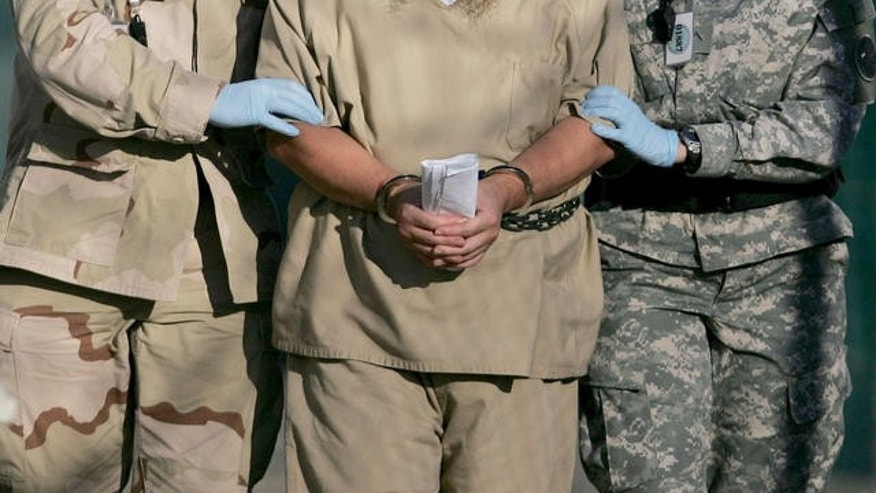 In this photo, reviewed by a U.S. Dept of Defense official, a shackled detainee is transported away from his annual Administrative Review Board hearing with U.S. officials, at Camp Delta detention center, Guantanamo Bay U.S. Naval Base, Cuba, Wednesday, Dec. 6, 2006. Each Guantanamo detainee has the option to participate in his own annual status review hearing which is part of the process for determining if a given detainee will continue to be held for another year. (AP Photo/Brennan Llinsley)