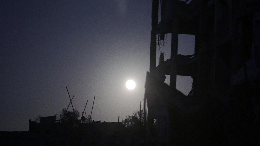 FILE- In this Monday, Aug. 11, 2014 file photo, a full moonshines on the destroyed al-Nada Towers residential neighborhood in the town of Beit Lahiya, northern Gaza Strip. Dozens of residents the al-Nada Towers took advantage of the latest truce to visit their homes, salvage what they can and exchange tips on how best to seek and secure compensation for their homes. (AP Photo/Khalil Hamra, File)