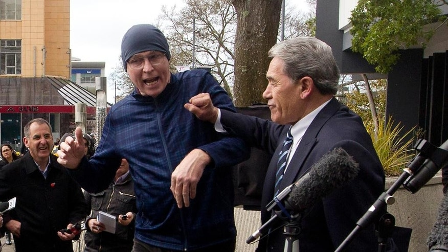 "New Zealand First party leader Winston Peters, right, pushes off a heckler while speaking to the media outside the Hamilton City Council Building at Garden Place in Auckland, New Zealand Thursday, Aug. 14, 2014. At the Aug. 10 campaign launch for his anti-immigration New Zealand First party, Peters lit into the government for allowing farms to be sold to foreign buyers, including those from China. ""As they say in Beijing, two Wongs don't make a white,"" he said, drawing laughter from his Auckland audience but condemnation elsewhere. (AP Photo/New Zealand Herald, Dean Purcell) NEW ZEALAND OUT, AUSTRALIA OUT"