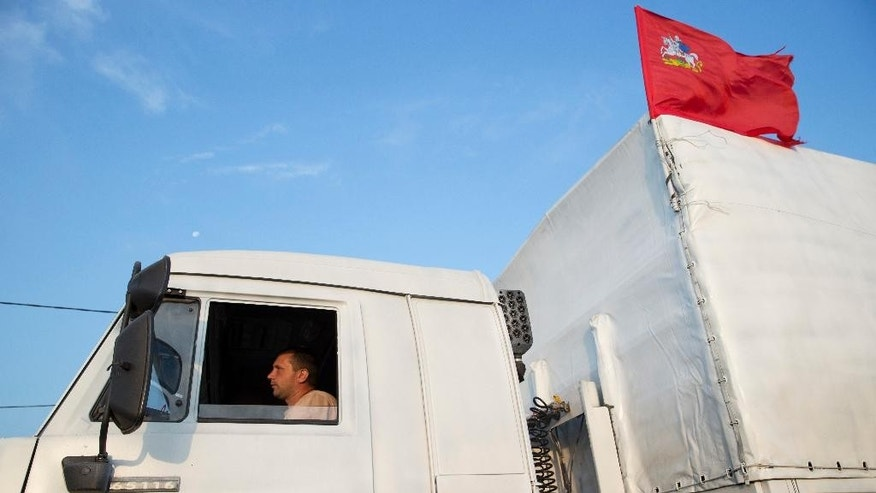 A white truck with humanitarian aid is driven from Voronezh towards Rostov-on-Don, Russia, early Thursday, Aug. 14, 2014. Russia on Tuesday dispatched some hundreds of trucks, although only a small proportion were counted in this convoy, covered in white tarps and sprinkled with holy water on a mission to deliver aid to a rebel-held zone in eastern Ukraine. (AP Photo/Pavel Golovkin)