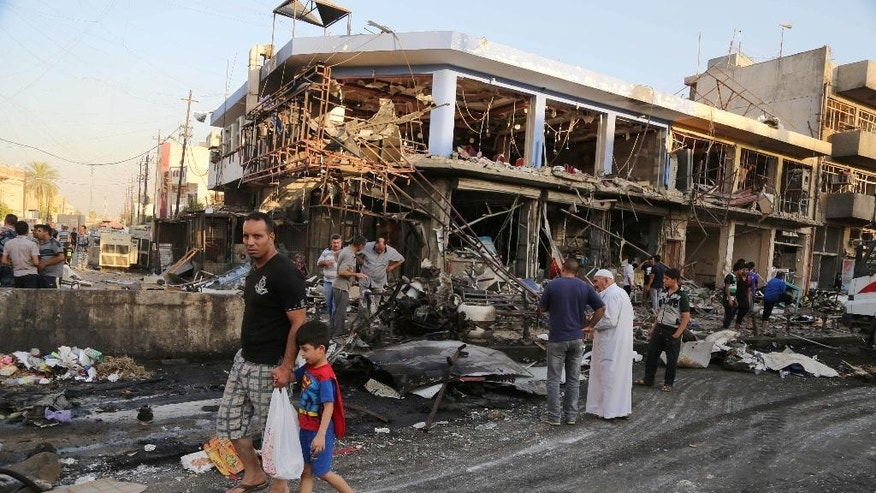 Civilians inspect the site of a car bomb attack near a restaurant in the southeastern district of New Baghdad, Iraq, Wednesday, Aug. 13, 2014. A string of attacks in and around the capital killed more than a dozen and wounded dozens. (AP Photo/Karim Kadim)
